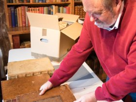 The curator at Little Hall Lavenham returning the books to the shelves landscape